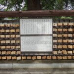 Plaques line a tree within the shrine complex where visitors request blessings